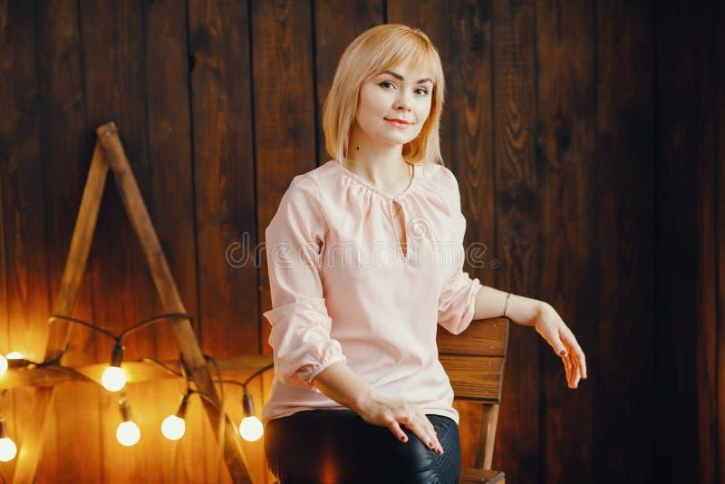 Blondes Mädchen, das auf einem Stuhl sitzt stockfotos