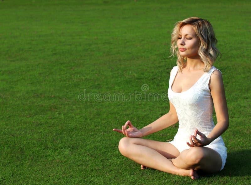 Blondes Mädchen, das auf grünem Gras meditiert. Schöne Sitzplätze der jungen Frau in der Yogahaltung von Lotos im Park stockbilder