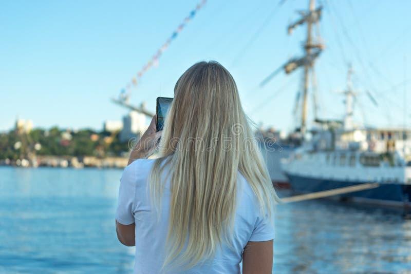 Blondes Mädchen, das Fotos von Segelschiffen im Seehafen macht stockfoto