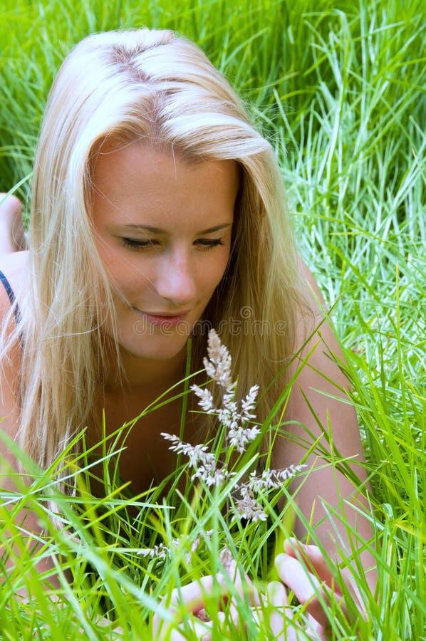 Blondes Mädchen, das Grasstartwert für zufallsgeneratorkopf in der Wiese studiert lizenzfreies stockfoto