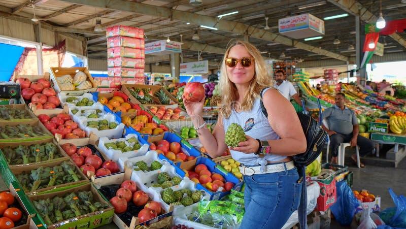 Blondes Mädchen, das organischen exotischen Fruchtflaschenbaum und pomegranate0 auf lokalem Basar kauft lizenzfreies stockfoto