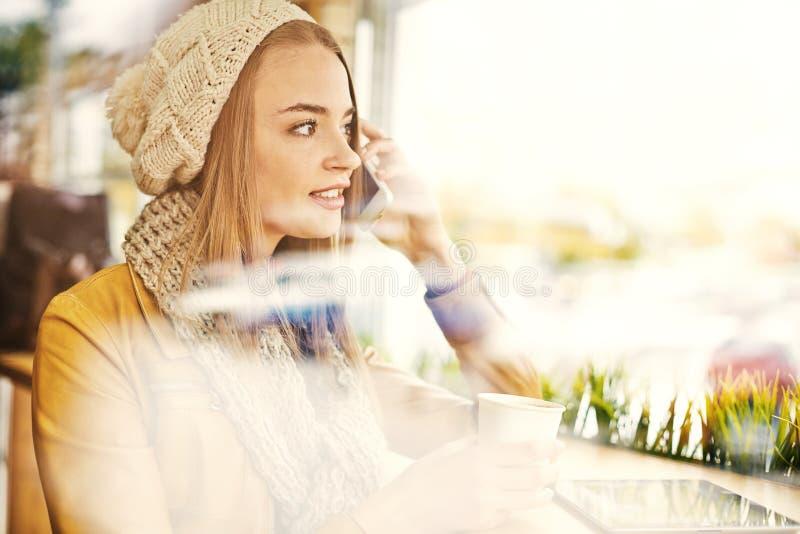 Blondes Mädchen, das am Telefon im Café spricht stockbilder