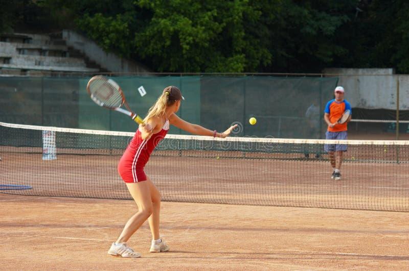 Blondes Mädchen, das Tennis spielt stockbilder