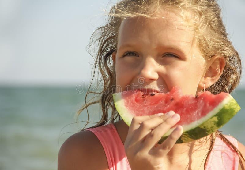 Blondes Mädchen, das Wassermelone isst stockfotografie