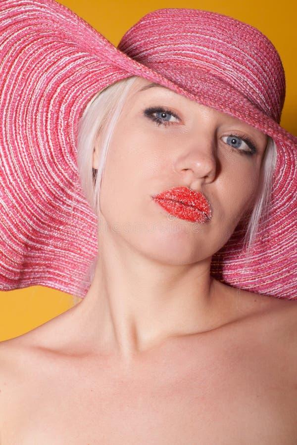Blondes Mädchen in den rosa Hutrotlippen stockfoto