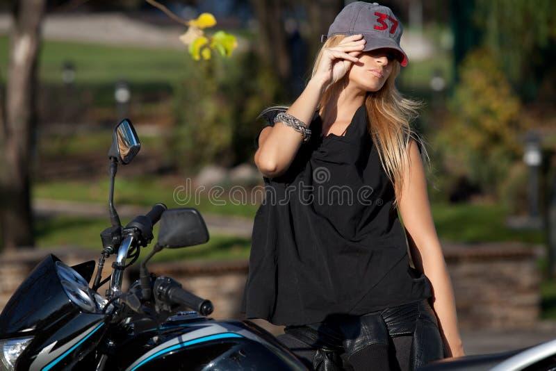 Blondes Mädchen in der Baseballmütze nahe Motorrad stockfotografie