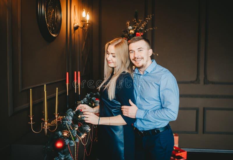 Blondes Mädchen in der blauen Kleider- und des gut aussehenden Manneshaltung in einem gemütlichen Raum mit Weihnachten verzieren lizenzfreie stockfotografie