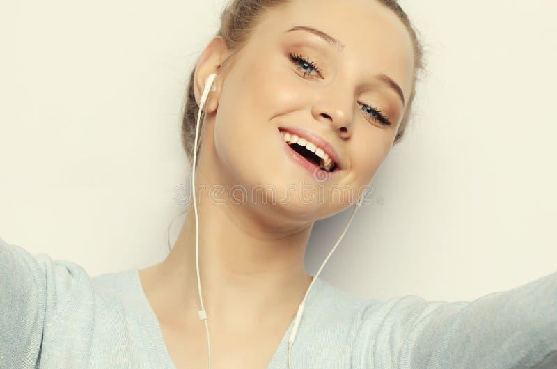 Blondes Mädchen in der hörenden Musik der Kopfhörer, die Foto macht stockfotografie