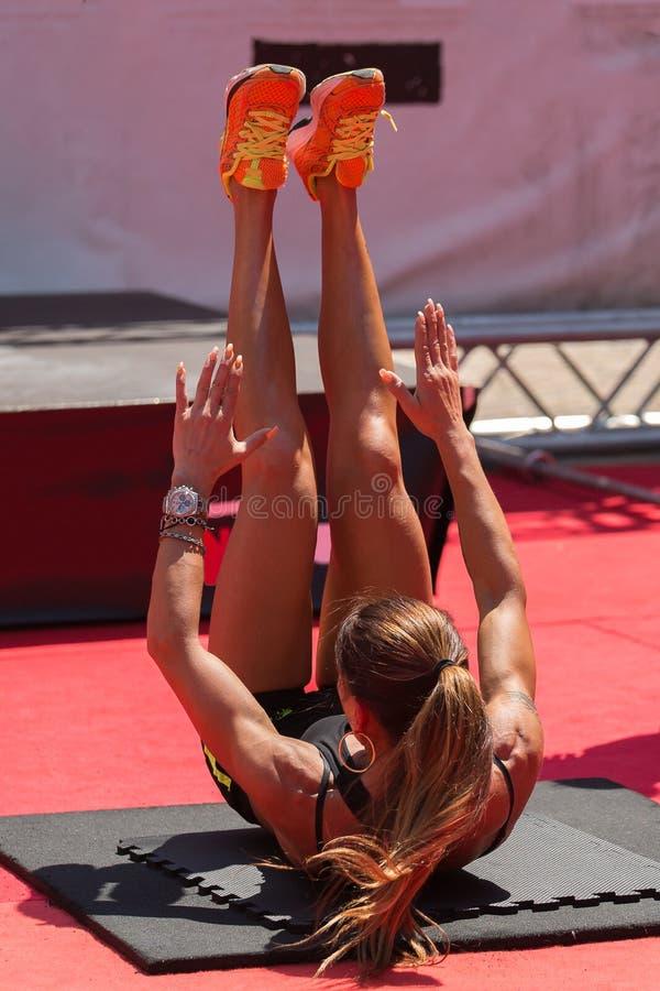 Blondes Mädchen in der schwarzen Sportkleidung, die Eignung tut, trainiert auf Mat Outdoor an der Turnhalle stockbilder