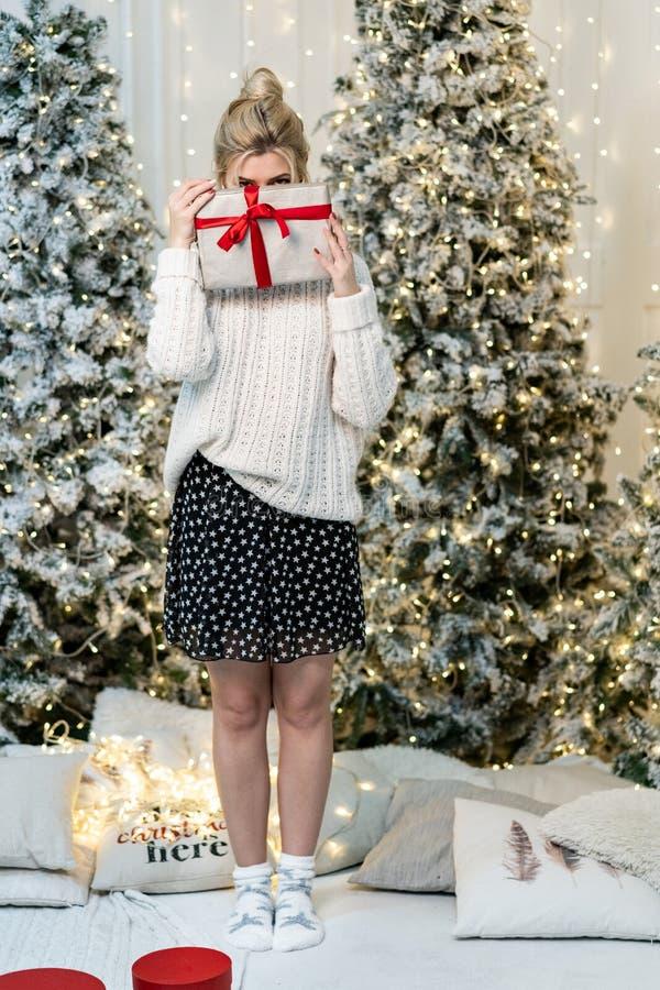 Blondes Mädchen in der weißen Strickjacke versteckt das Gesicht hinter dem Geschenk lizenzfreie stockfotos