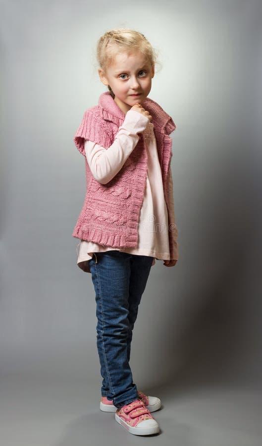 Blondes Mädchen in der zufälligen Kleidung in voller Länge auf grauem Hintergrund lizenzfreie stockfotos