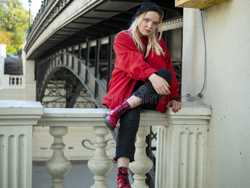 Blondes Mädchen des jungen Hippies in einem gestrickten schwarzen Hut und in einer roten Jacke, die unter einer Brücke sitzen lizenzfreies stockbild