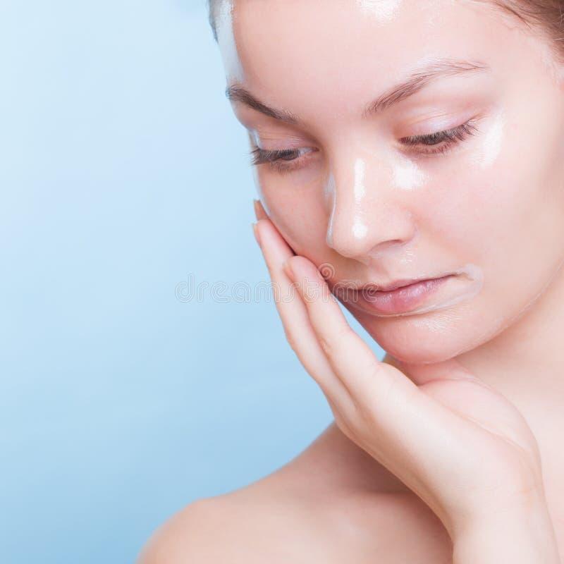 Blondes Mädchen des Porträts in der Gesichtsmaske auf Blau. Schönheit und Hautpflege. lizenzfreie stockfotos