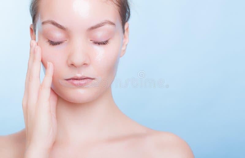 Blondes Mädchen des Porträts in der Gesichtsmaske auf Blau. Schönheitshautpflege. lizenzfreie stockfotos