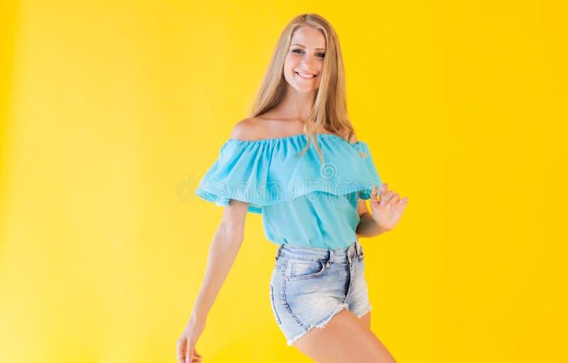 Blondes Mädchen in einem blauen Kleid, auf einem gelben Hintergrund lizenzfreie stockbilder