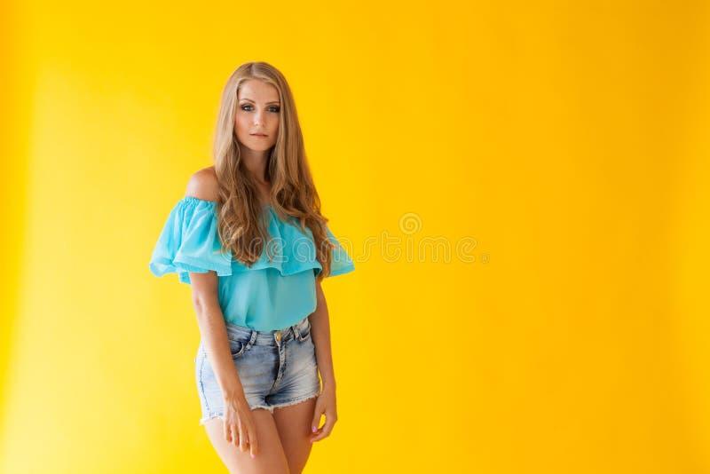 Blondes Mädchen in einem blauen Kleid, auf einem gelben Hintergrund stockfotos