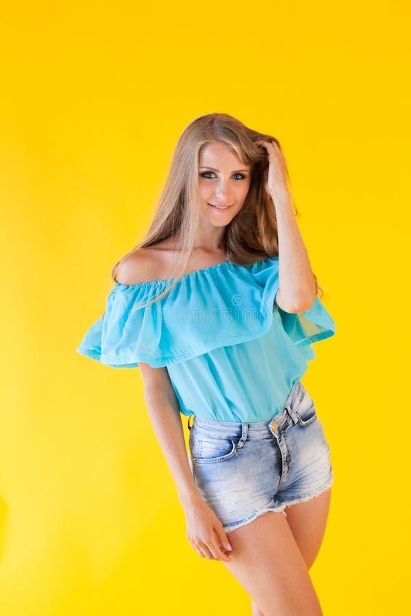 Blondes Mädchen in einem blauen Kleid, auf einem gelben Hintergrund stockbilder