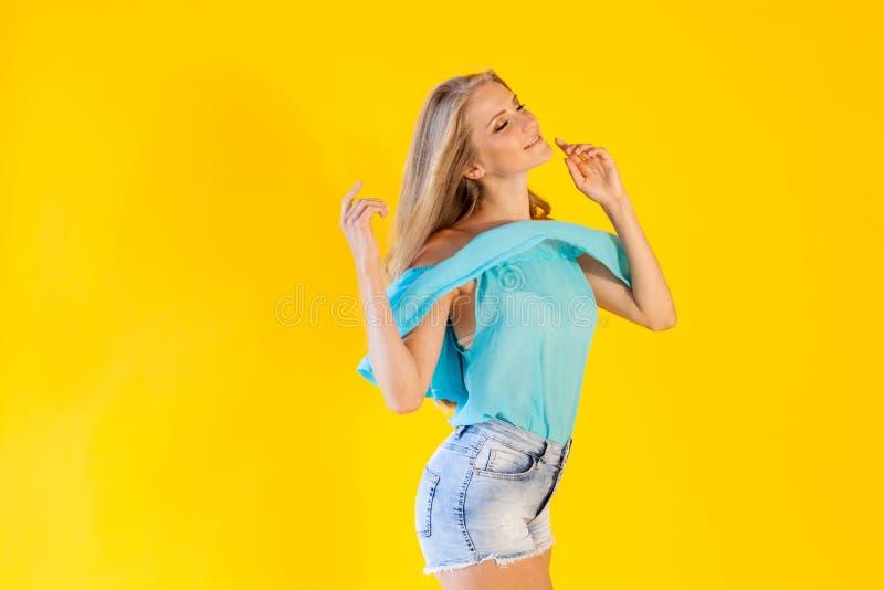 Blondes Mädchen in einem blauen Kleid, auf einem gelben Hintergrund stockbild