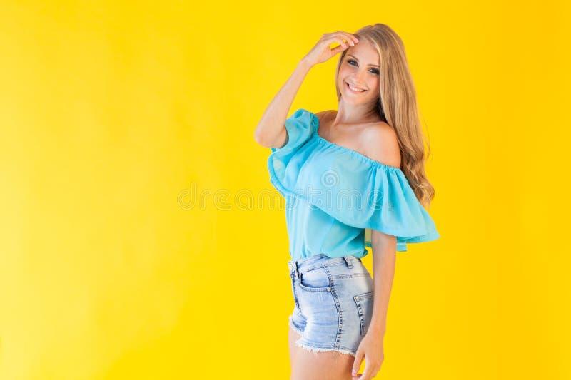 Blondes Mädchen in einem blauen Kleid, auf einem gelben Hintergrund lizenzfreie stockfotografie