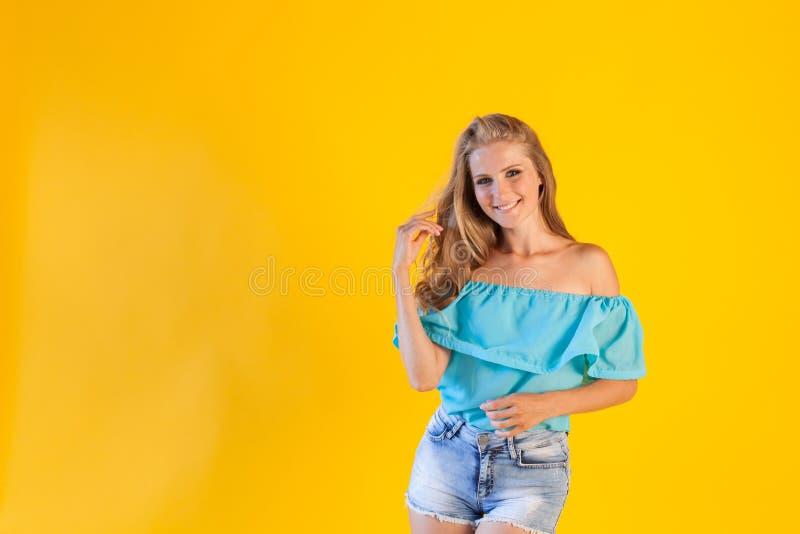 Blondes Mädchen in einem blauen Kleid, auf einem gelben Hintergrund lizenzfreies stockfoto