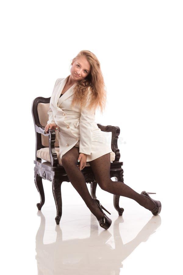 Blondes Mädchen in einer weißen Jacke und in schwarzen Strümpfen sitzt in einem Stuhl stockfotografie