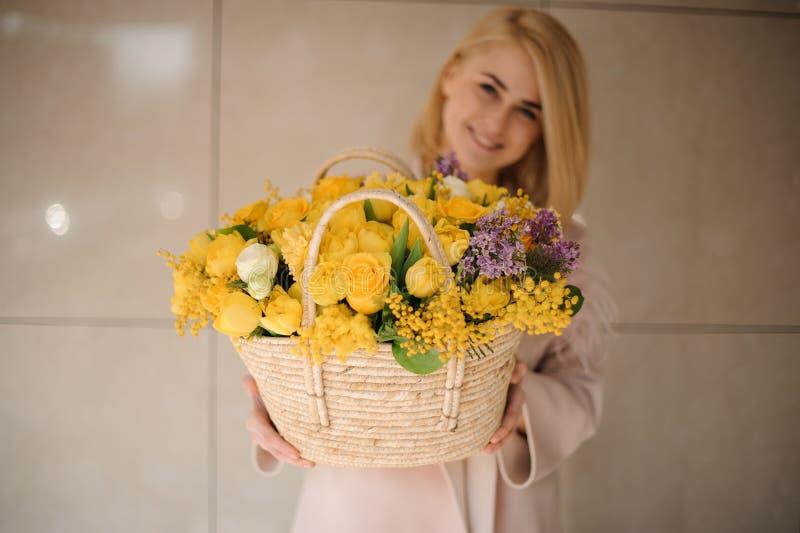 Blondes Mädchen hält Blumenstrauß von gelben Blumen im Korb stockfotografie