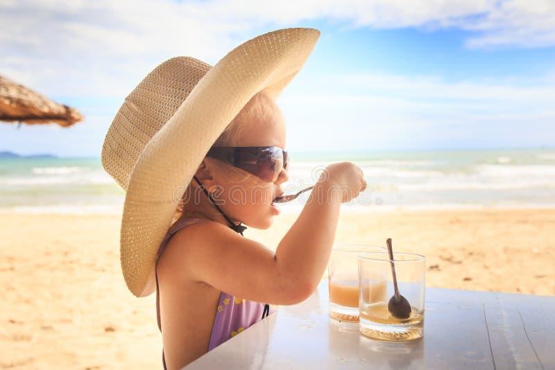 Blondes Mädchen im Großen Hut-Sonnenbrille-Getränk-Saft mit Löffel stockfotos