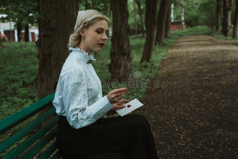 Blondes Mädchen im Park einen Papierbrief lesend stockfotos