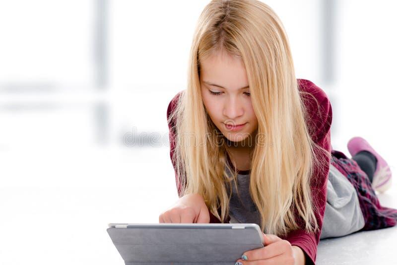 blondes m dchen mit dem tabletten pc der auf dem boden liegt stockbild bild von person. Black Bedroom Furniture Sets. Home Design Ideas