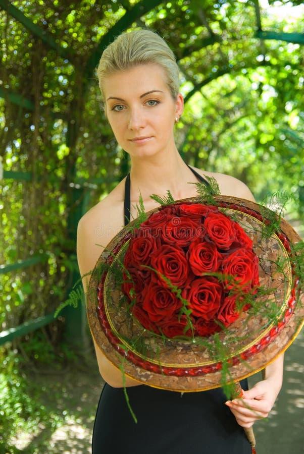 Blondes Mädchen mit einem Blumenstrauß lizenzfreies stockfoto