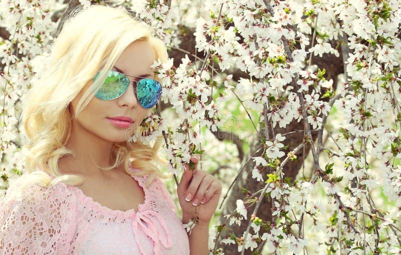Blondes Mädchen mit Flieger Sunglasses über Cherry Blossom. Frühling lizenzfreies stockbild
