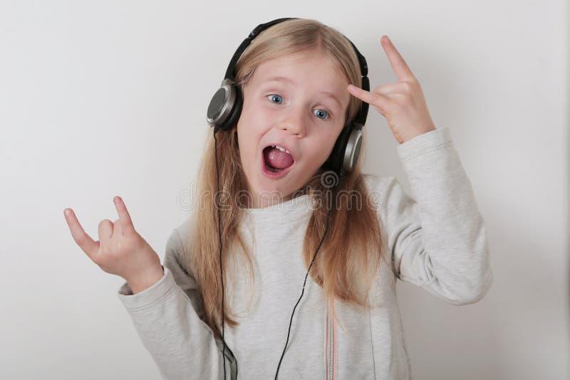 Blondes Mädchen mit hörender Musik und dem Gesang der Kopfhörer Nettes kleines Mädchen, das ein Stein-nrollenzeichen macht lizenzfreie stockbilder