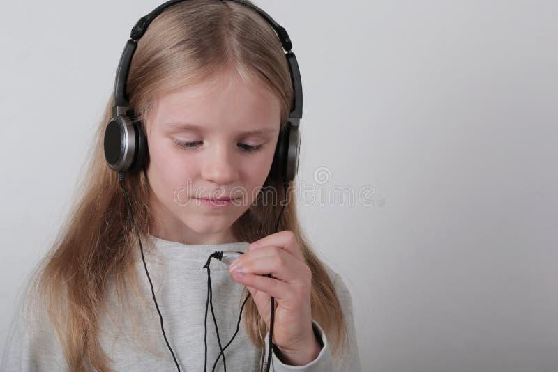 Blondes Mädchen mit hörender Musik und dem Gesang der Kopfhörer Nettes kleines Mädchen, das ein Stein-nrollenzeichen macht lizenzfreies stockbild