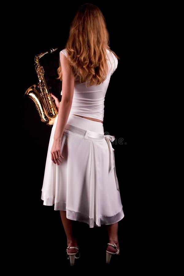 Blondes Mädchen mit Saxophonstellung drehte sich zurück stockfotografie