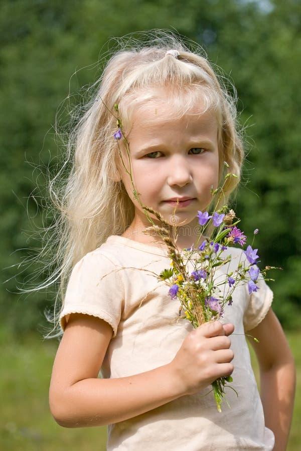 Blondes Mädchen mit wilden Blumen stockfotos