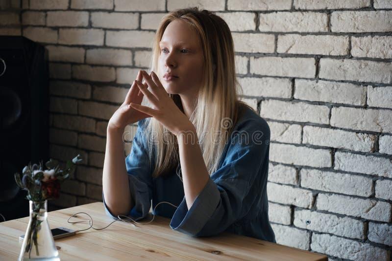 Blondes Mädchen sitzt mit Kopfhörern und untersucht durchdacht den Abstand und kombiniert vor ihren Fingern stockfotografie