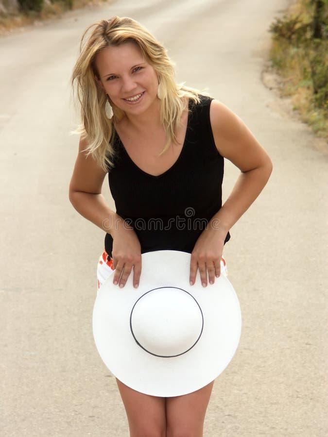 Blondes Mädchen umfaßt ihre Fahrwerkbeine mit weißem Hut stockbilder