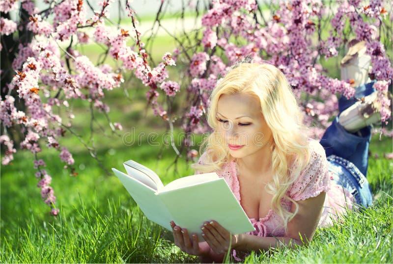 Blondes Mädchen, welches das Buch unter Cherry Blossom liest stockfotografie
