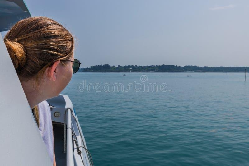 Blondes Mädchen, welches das Meer von einem Boot betrachtet stockfotografie