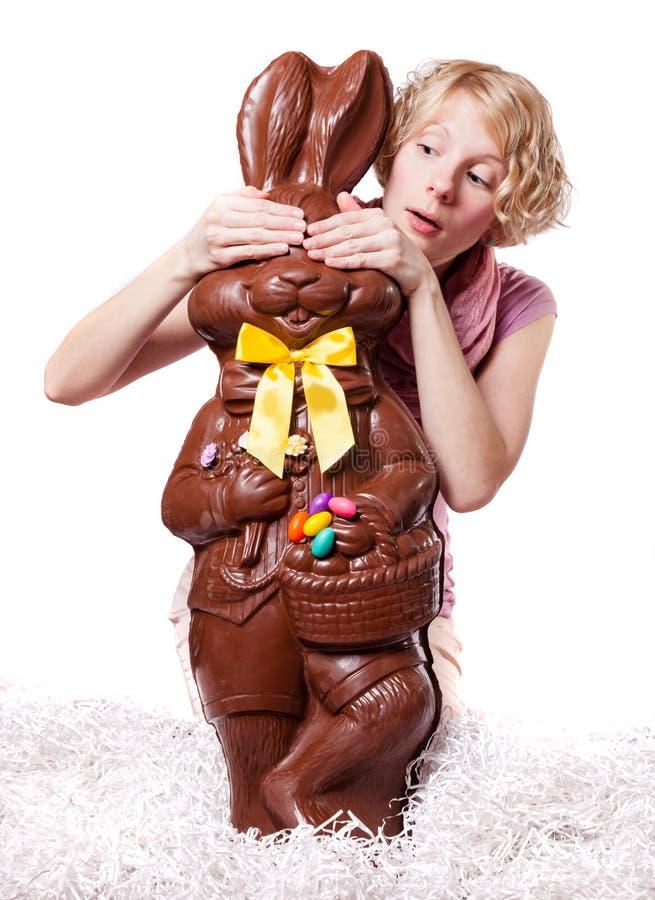 Blondes Mädchen, welches die Augen eines Schokoladen-Häschens versteckt lizenzfreies stockbild