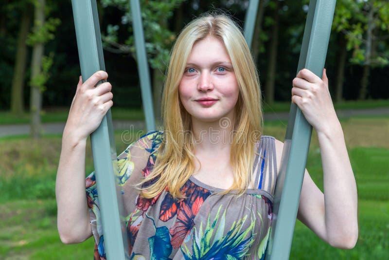 Blondes Mädchen zwischen grünen Metallrohren lizenzfreies stockfoto