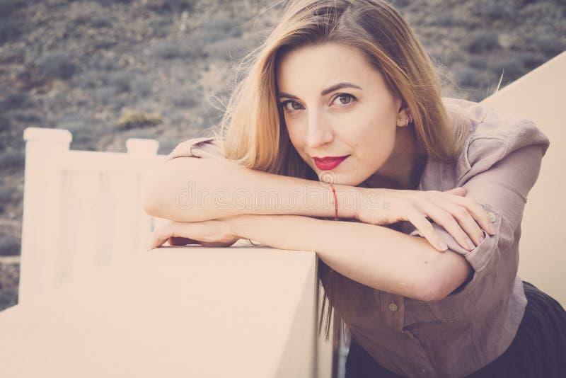 Blondes M?dchen mit dem langen Haar, die Augen, die, mit Bluse und gefaltetem Rock in der Terrasse geschlossen werden, atmet gest lizenzfreies stockfoto