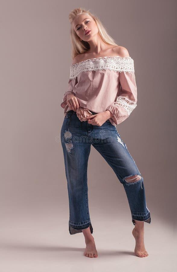 Blondes Modell in der Bluse und in Jeans, die auf rosa Hintergrund aufwerfen stockfotografie