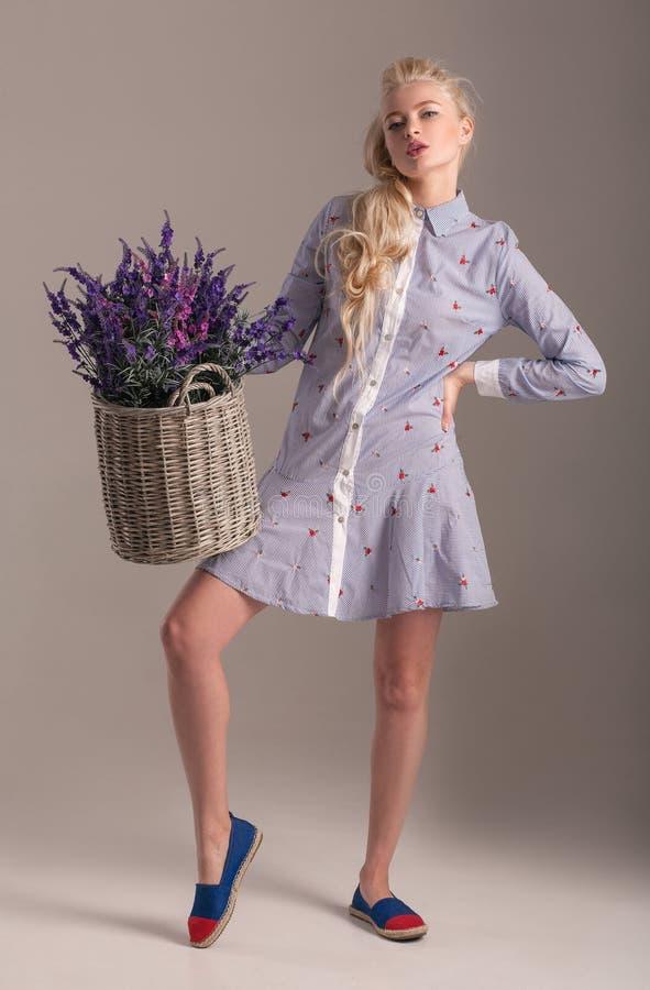 Blondes Modell im Kleid, das mit Korb von Blumen in ihren Händen aufwirft stockfoto