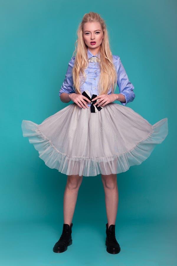 Blondes Modell im transparenten Kleid und Stiefel, die auf blauem backg aufwerfen stockbild