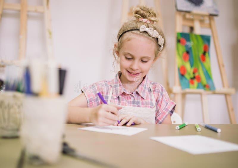 Blondes nettes lächelndes siebenjähriges Mädchen, zeichnet am Tisch im kreativen Studio stockfoto