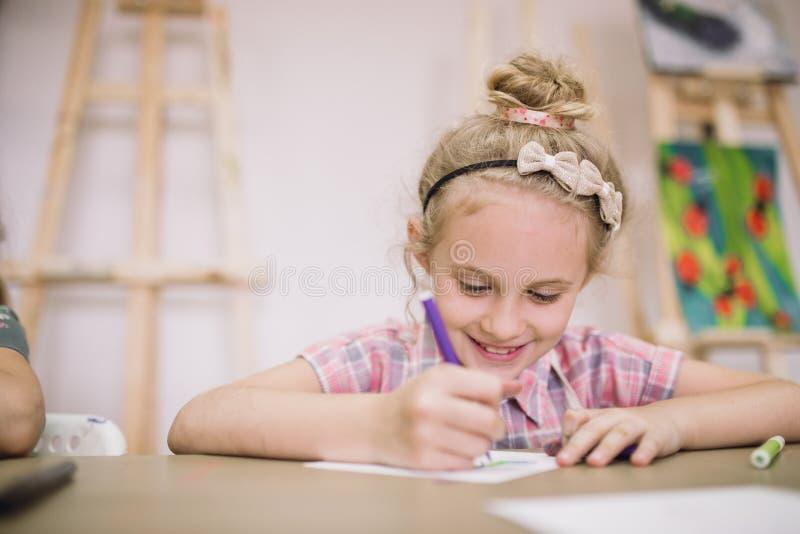 Blondes nettes lächelndes siebenjähriges Mädchen, zeichnet am Tisch im kreativen Studio lizenzfreie stockfotografie