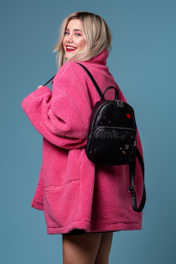 Blondes nettes Mädchen, das im stilvollen rosa Mantel im Studio mit schwarzem Rucksack aufwirft lizenzfreies stockbild