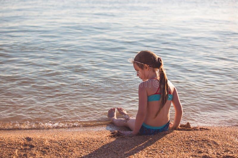 Blondes nettes Mädchen mit sieben Jährigen, das auf dem Strand während der Ferien sitzt stockfotos