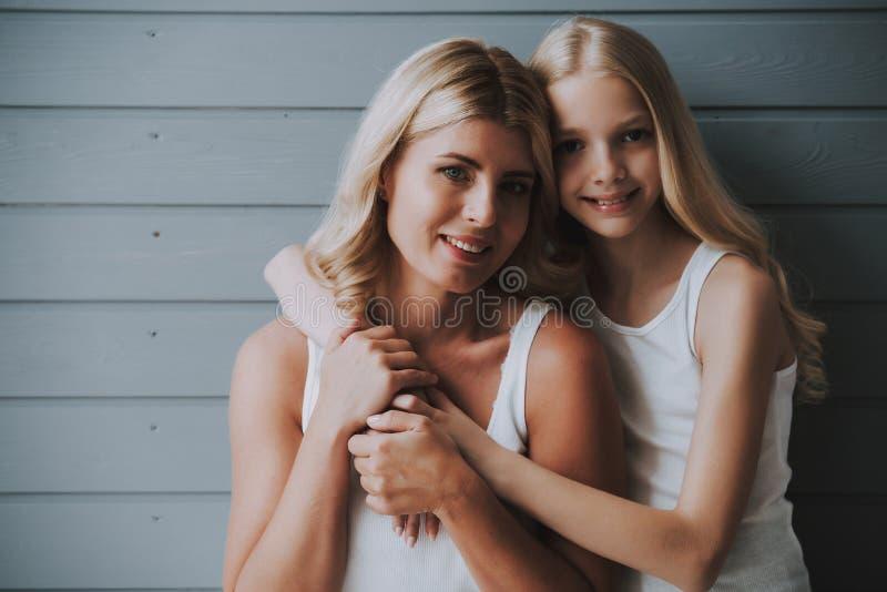 Blondes nettes Mädchen umarmt blonde Mutter auf hölzernem Hintergrund lizenzfreie stockbilder